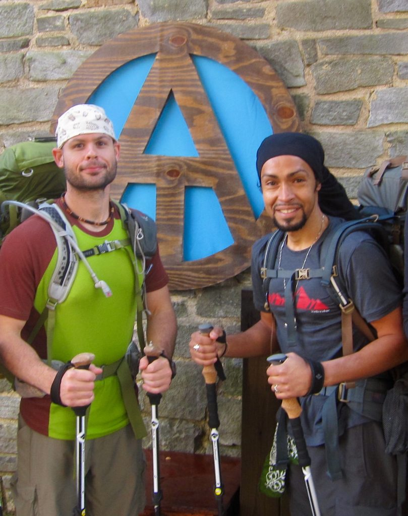 The White Shadow & His Dark Companion, two thru-hikers standing in front of an AT sign at Mountain Crossings Outfitter