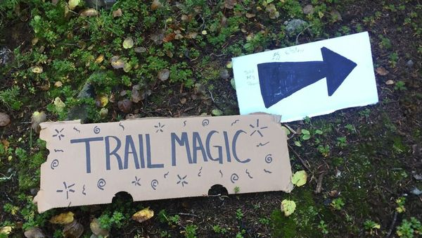 Trail Magic sign written on cardboard and an arrow pointing to it.